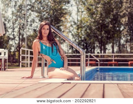 One Young Adult Woman Caucasian Model Posing, Long Hair, Sitting On Swimming Pool Edge, Swimwear, On