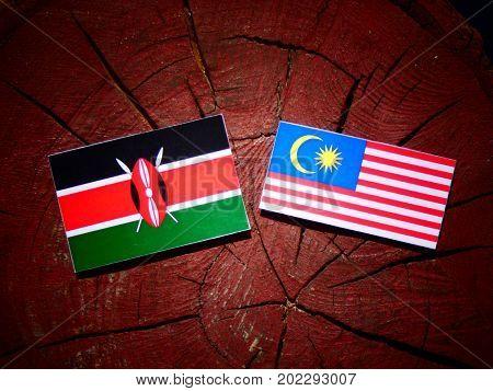 Kenyan Flag With Malaysian Flag On A Tree Stump Isolated