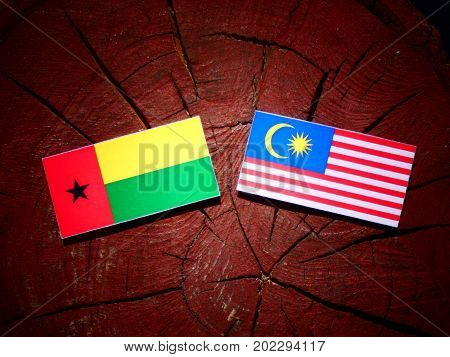 Guinea Bissau Flag With Malaysian Flag On A Tree Stump Isolated