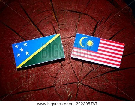 Solomon Islands Flag With Malaysian Flag On A Tree Stump Isolated