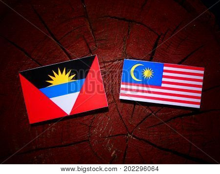 Antigua And Barbuda Flag With Malaysian Flag On A Tree Stump Isolated