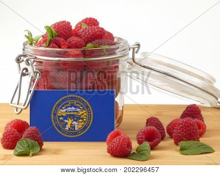 Nebraska Flag On A Wooden Panel With Raspberries Isolated On A White Background
