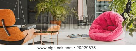 Opened book on white carpet near to red pouf in designed living room with palms