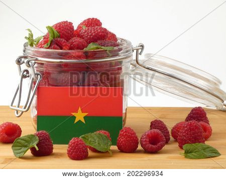 Burkina Faso Flag On A Wooden Panel With Raspberries Isolated On A White Background