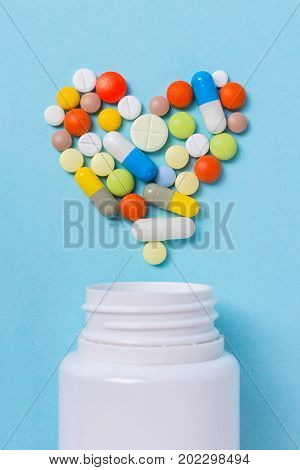 Assorted pharmaceutical medicine pills tablets and capsules for the treatment of heart disease. Heart shape and bottle of pills.