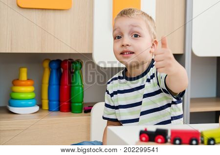 Happy Boy Sitting At Table And Showing Thumb Up Gesture