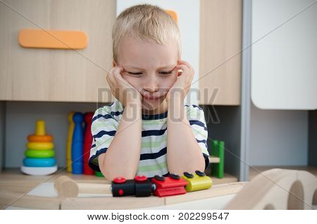 Bored sad little boy sitting at table. sad bored boy child toy activity baby kindergarten concept