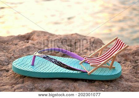 flipflop with beachchair on a stone close up behind the sea