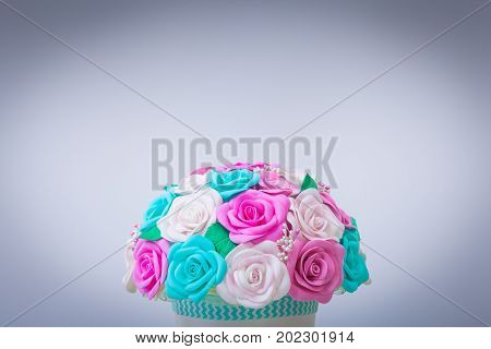close-up of artificial flowers of roses from foam in different colors of blue pink white in a white pot made with their own hands for decorating weddings interiors and holidays on a swivel table