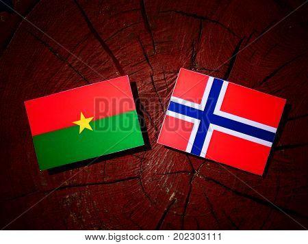 Burkina Faso Flag With Norwegian Flag On A Tree Stump Isolated