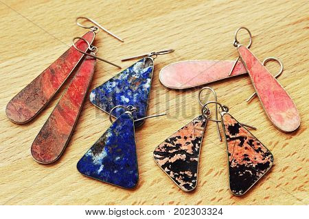 Earrings from natural ornamental stones on wooden background