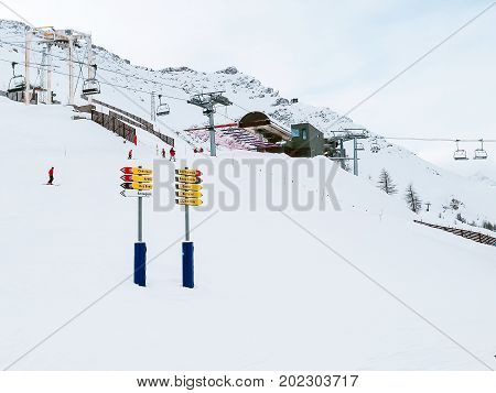 Courmayeur, Italy - January 27, 2015: Skiers and snowboarders at ski slopes in the mountains of winter resort. Panoramic view of Courmayeur, Italian Alps.