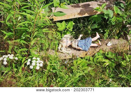 Forgotten old doll on wooden steps among plants