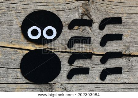 Creating a felt Halloween spider ornament. Step. Cut black and white felt details to create Halloween spider toy. Felt projects for beginners and kids. Old wooden background. Top view. Closeup