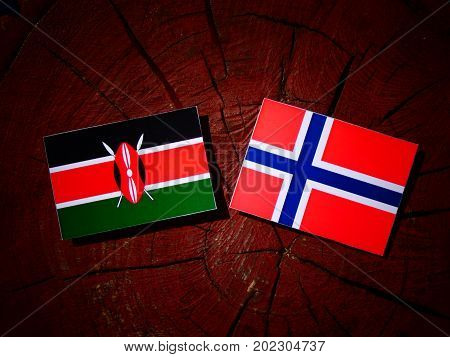 Kenyan Flag With Norwegian Flag On A Tree Stump Isolated