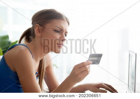 Beautiful serious young woman holding credit card in hand, attentively reading it number, typing on laptop, making purchases in Internet. Pretty lady using online banking service for sending payments