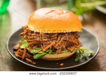 Sweet bun barbecue beef brisket bun with watercress leaves. Whisky barrel chip smoked British beef brisket with smoky barbecue sauce.