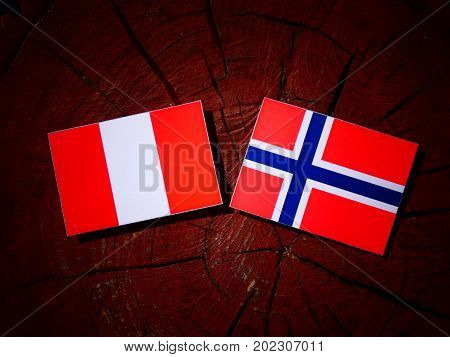 Peruvian Flag With Norwegian Flag On A Tree Stump Isolated