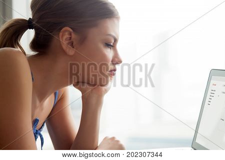 Serious young woman reading e-mail letter on laptop screen , feeling bored, lack of energy, doing boring work. Unhappy lady writing message, sending resume, examines online correspondence. Close up
