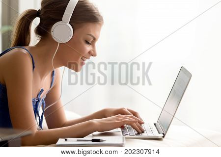 Side view portrait of smiling young woman in headphones typing on laptop while taking online course or personal training for self-education, qualification increase. Happy lady studying in Internet