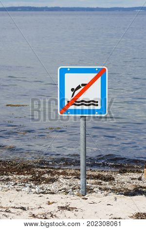 Prohibition sign next to old wooden pier in Langeland, Denmark forbidding jumping from the pier