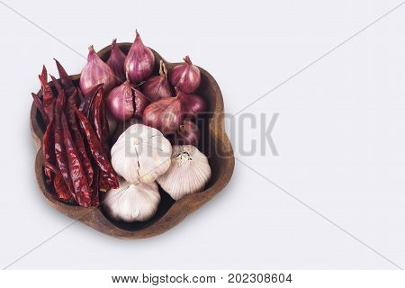 Thai spices on wooden plate. Dried chilies shallots and garlic isolate on white background with clipping path