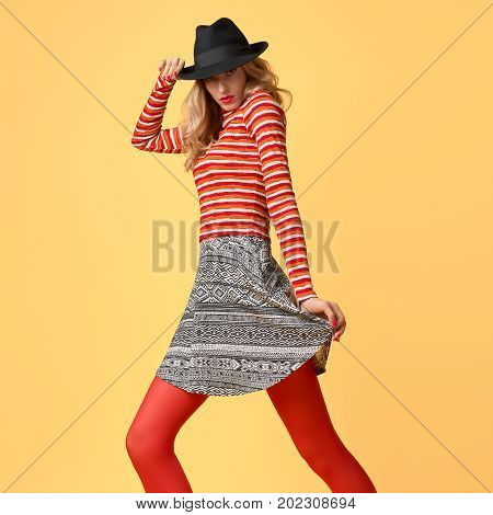 Fall Fashion. Model Woman in Autumn Fashion Outfit Having Fun. Stylish Sweater Trendy Hat in red fashion pantyhose. Glamour Playful Blonde Sexy girl, Wavy Hairstyle, Fashion Pose, Makeup. Fall Autumn