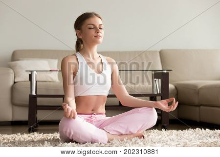 Pretty young woman in sportswear meditating in lotus position on carpet in living room. Beautiful lady relieving stress, concentrating on positive thoughts with practicing yoga and spiritual session