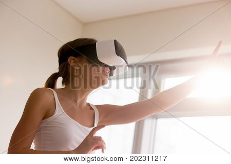 Woman in VR headset reaching out hand and touching objects in virtual reality, pointing on invisible buttons in simulated world, selecting menu items in virtual interface, watching interactive video