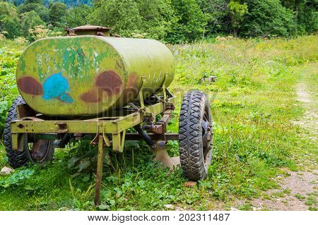 Old barrel for drinking water on wheels. Water tank trailer.