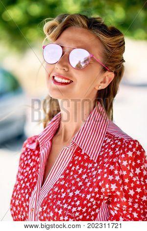 Beautiful blonde woman wearing sun glasses glasses posing outdoors
