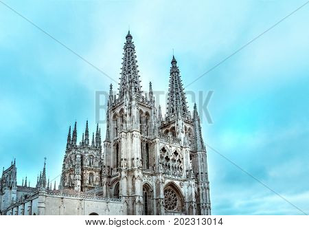 A photo of the famous gothic cathedral in Burgos, Spain, in the morning light in the teal blue sky, with a place for text