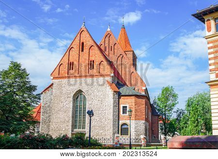 View of old stone Catholic parish building  with orange brick roof, arcade window and blooming tea rose bush on a sunny summer day, Poland, Krakow