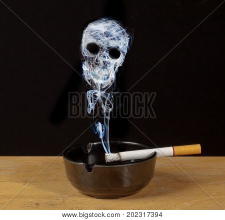Burning cigarette in an ashtray with a skull formed of smoke a warning of the hazards of smoking
