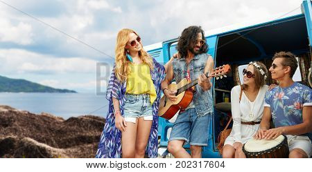 summer holidays, road trip, travel and people concept - happy young hippie friends with guitar and drum playing music at minivan car over island background