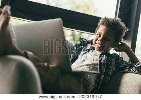 Boy With Laptop In Armchair