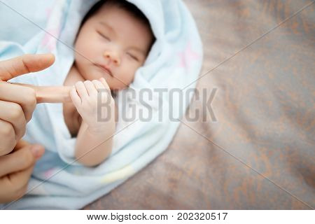 Concept of love and family relationship : close up newborn Asian baby hand hold round of mother finger with copy space at right side. Asia baby portrait .