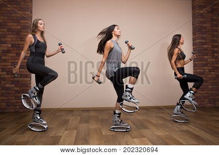 Three Beautiful And Sport Girl In The Gym Training. Kangoo Jumping. Beautiful Girls In Kangoo Jumpin