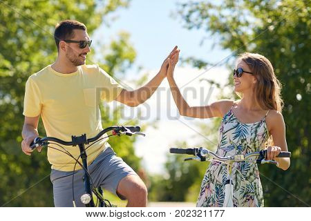 people, leisure and lifestyle concept - happy young couple with bicycles at country making high five