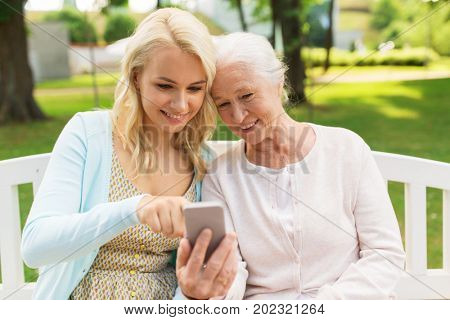 family, generation and people concept - happy smiling young daughter and senior mother with smartphone sitting on park bench