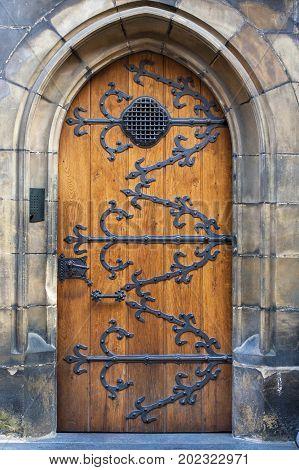 Medieval door with metal decoration. Wooden old door closed