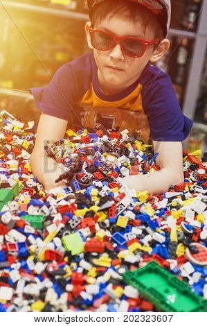 Boy in glasses play with many toys. Constructor playthings in hands of kid