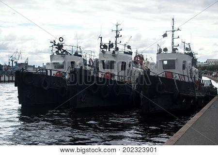 Image of three port tugs on the river. Neva. Saint-Petersburg.