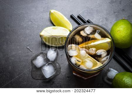 Cuba libre on dark background. Traditional summer alcohol iced drink. Top view copy space.