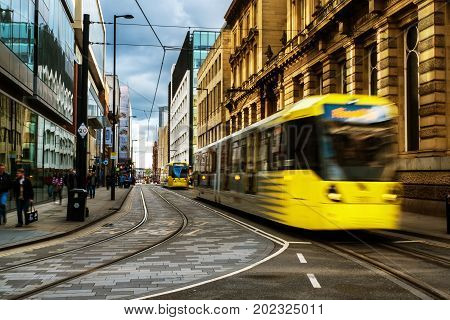 Manchester, UK. Light rail yellow tram in the city center of Manchester, UK in the evening. It is a popular transportation in Manchester.