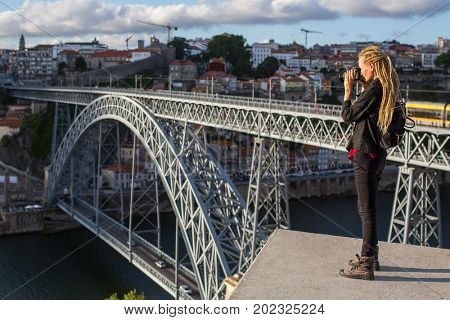 Young woman with dreadlocks takes pictures on the viewing platform opposite the Dom Luis I bridge across the Douro river in Porto, Portugal.