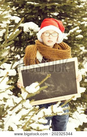 Small Santa Boy With Blackboard In Winter Outdoor