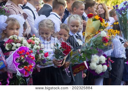 Adygea Russia - September 1 2017: children with bouquets of flowers enrolled in the first grade with high school students at school the solemn ruler in day of knowledge