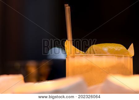 Whiskey sour garnished with lemon detail. Candlelit alcoholic drink on shelf with lemon peel on top