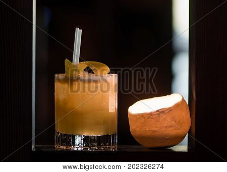 Whiskey sour garnished with lemon in old fashioned glass. Candlelit alcoholic drink on shelf with lemon peel on top